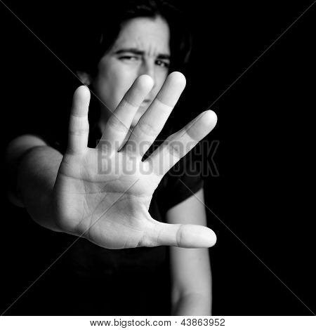 Black and white portrait of a frightened woman extending her hand trying to stop any coming danger on a black background