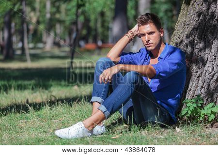 young casual man sitting on the ground and leaning to a tree trunk while looking down with a pensive expression