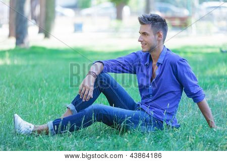 young casual man sitting in the grass and looking away from the camera with a smile on his face