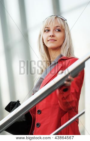 Young business woman on the steps against office windows
