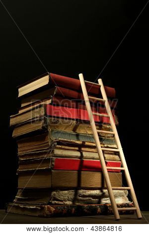 Old books and wooden ladder, on black background
