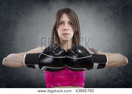 Young beautiful woman with boxing gloves at workout over rusty background