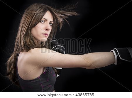 boxer woman during boxing exercise making direct hit with black gloves