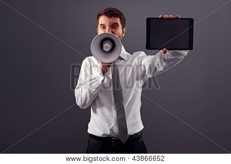emotional businessman showing the screen of tablet pc and shouting with megaphone against grey background