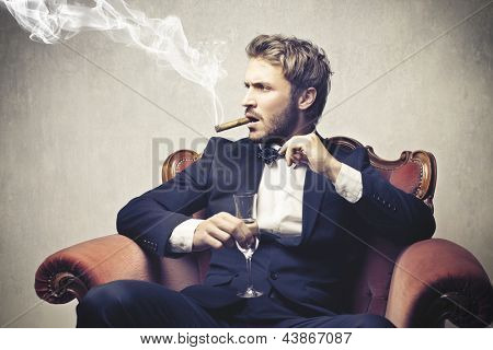 boss smokes cigar with a glass of champagne