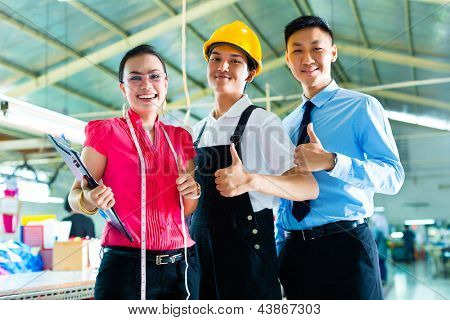 Shift supervisor or foreman, together with the owner or CEO and the designer, look at a draft for the new collection, they standing in Chinese textile factory