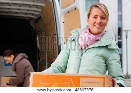 Two young women loading into a moving truck, they carry moving boxes