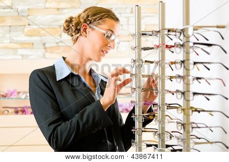 Young woman at optician with glasses, she might be customer or salesperson