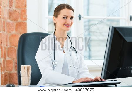 Young female doctor sitting at a desk in front of window in clinic writing or reading on a Computer or Pc