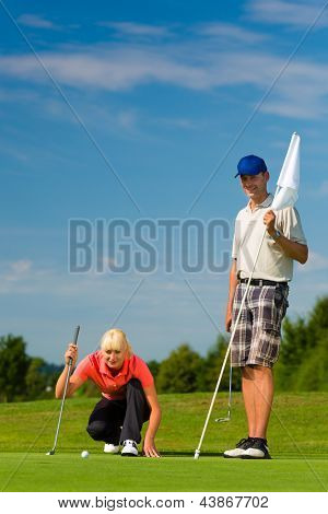 Young female golf player on course putting, she aiming for her put shot