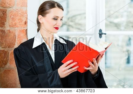 Young female lawyer working in her office reading in a typical law book