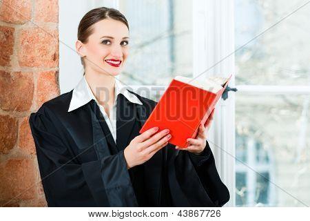 Jovem advogado feminino trabalhando em seu escritório, lendo um livro típico de lei