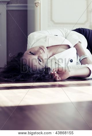 Sad young woman lying on the floor