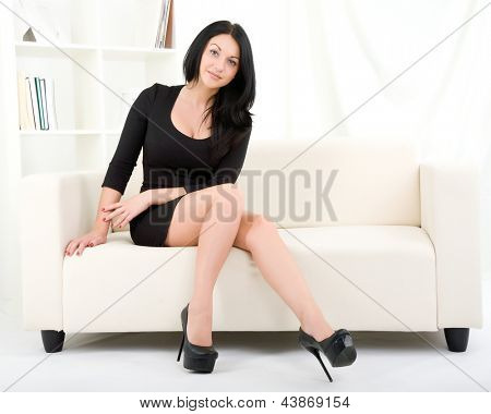 Beautiful girl in black dress sitting on the sofa
