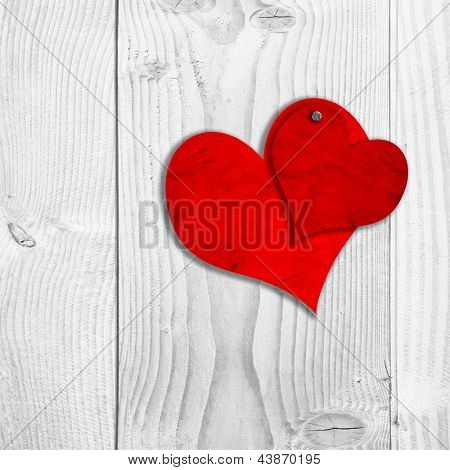 Concept or conceptual two red old paper vintage hearts nailed on white wood or wooden background as valentine card