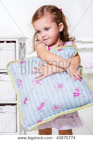 Adorable toddler girl holding pillow in hands