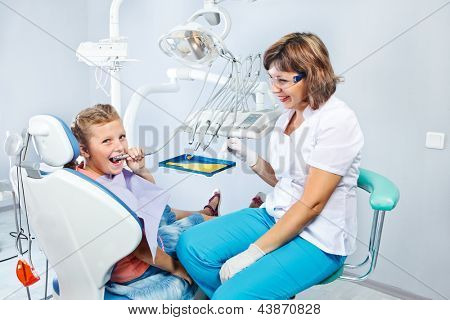 Kid playing with dental drill during  her first pediatric dentist visit