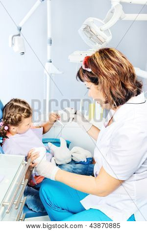 Dentist showing toy teeth to her little patient