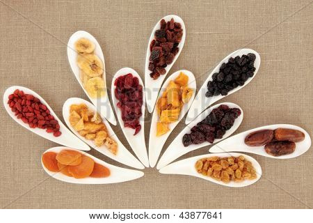 Dried fruit selection in white porcelain bowls over beige linen background.