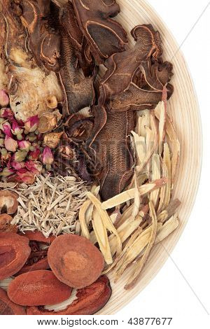 Traditional chinese herbal medicine selection on a round wooden bowl isolated over background.