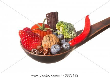 Antique wooden spoon filled with antioxidants fruits and vegetables