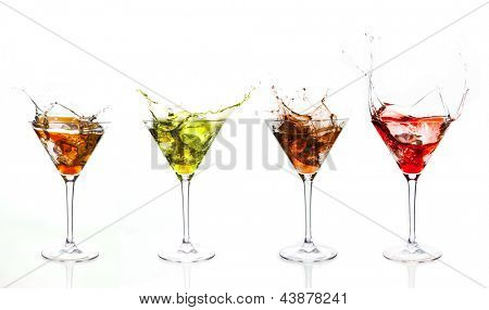 Serial arrangement of coloured liquids splashing in cocktail glass on white background