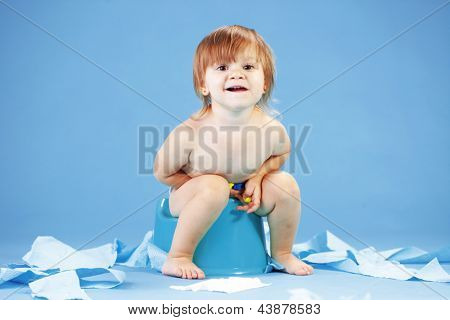 Studio shot of funny toddler sitting on potty chair