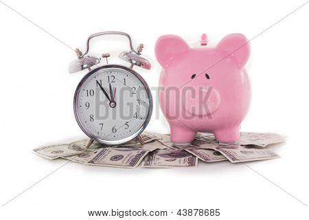 Piggy bank beside alarm clock on dollars on white backgroun