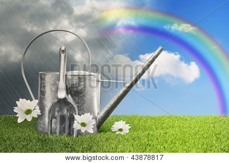 Watering can against a rainy sky turning to blue with a rainbow