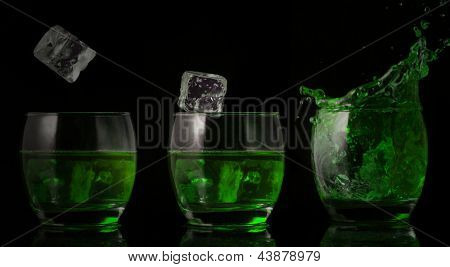 Serial arrangement of ice falling into glass of green liquid on black background
