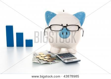 Blue and white piggy bank wearing glasses with calculator and cash and blue graph in background