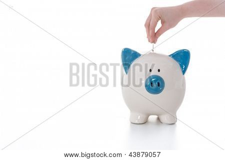Hand placing coin into blue and white piggy bank on white background