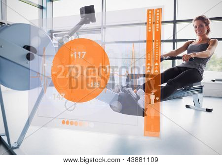 Young attractive girl on rowing machine with futuristic interface showing calories