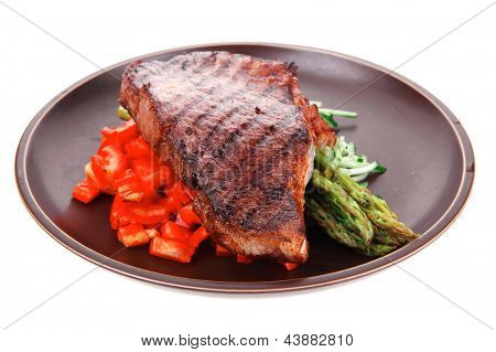 meat table : rare medium roast beef fillet with tomatoes and asparagus served on dish isolated over white