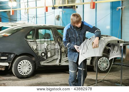 trabajador reparador profesional en industria automotriz lijado parachoques del coche de cuerpo plástico