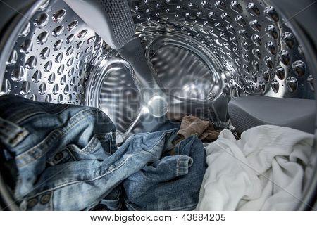 Vista interna del tambor de la lavadora llenado de ropa