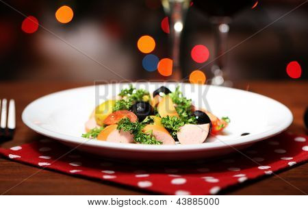 Tasty salad on dark background with bokeh  defocused lights
