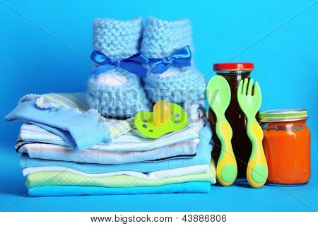 Pile of baby clothes on blue background