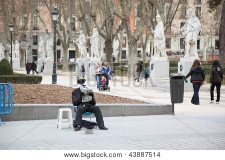 MADRID - MARCH 8: Beggar without head reads newspaper and asks alms near Royal Palace on March 8 2012 in Madrid, Spain. Unemployment in Spain is one of highest in European Union.