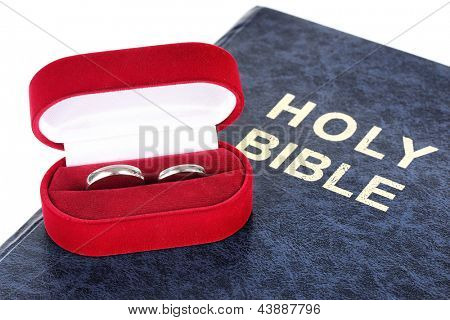 Wedding rings on bible isolated on white