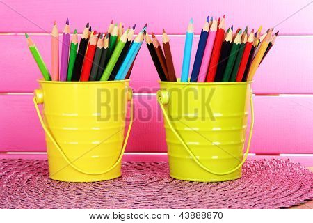 Colorful pencils in two pails on table on pink background