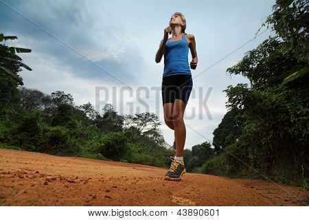 Young lady running on cross country road with earphones