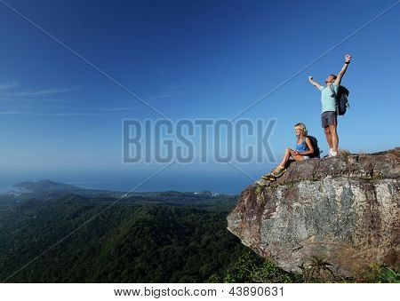 Young hikers with backpacks relaxing on top of a mountain and enjoying valley view
