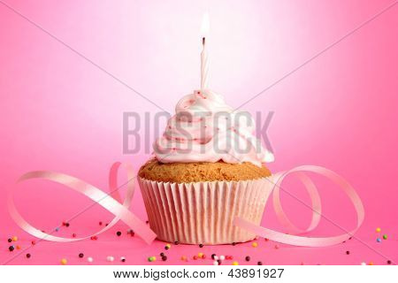 tasty birthday cupcake with candle, on pink background