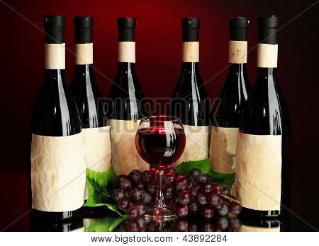 Composition of wine bottles, glass and  grape, on dark red background