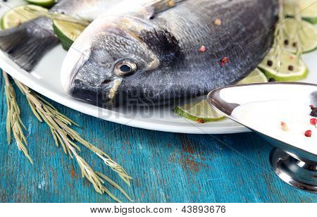 Two fish dorado with lemon on plate on blue wooden table close-up