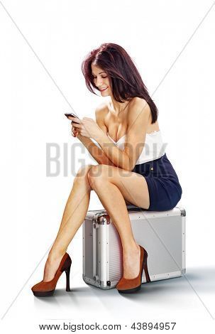 tourist girl seated on suitcase talking on mobile phone isolated on white background