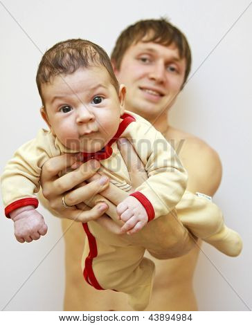 2 month old baby lying on fathers hand.