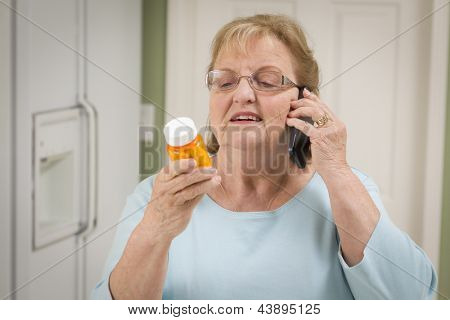 Beautiful Senior Adult Woman in Kitchen on Her Cell Phone Holding Prescription Bottle.