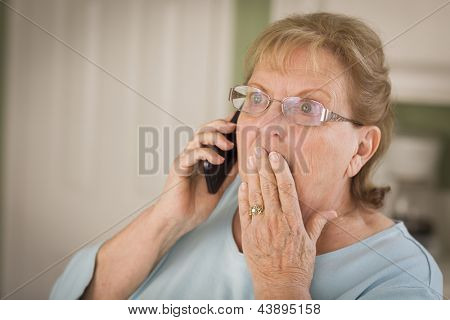 Shocked Senior Adult Woman on Cell Phone with Hand Over Mouth in Kitchen.